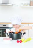 Little girl in chef hat cooking. Stock Image