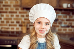 Little girl in chef hat and flour on face Royalty Free Stock Photo