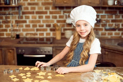 Little girl in chef hat making shaped cookies in kitchen Royalty Free Stock Photo