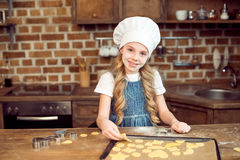 Little girl in chef hat making shaped cookies in kitchen Stock Image