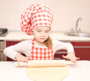 Little girl with chef hat rolling dough Royalty Free Stock Image