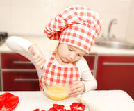 Little girl with chef hat stirrring cookie dough Royalty Free Stock Photo