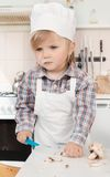 Little girl chef in the kitchen Stock Photos
