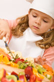 Little girl chef with lots of fruits Royalty Free Stock Photos