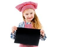 Little girl in chef uniform with blank paper Stock Photography