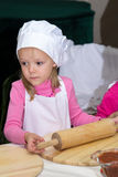 Little girl in chefs hat is cooking pizza Stock Photos