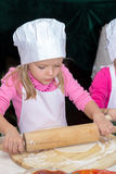 Little girl in chefs hat is cooking pizza Royalty Free Stock Image