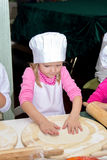 Little girl in chefs hat is cooking pizza Stock Images