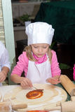 Little girl in chefs hat is cooking pizza Royalty Free Stock Photo