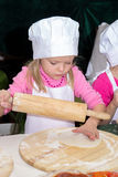 Little girl in chefs hat is cooking pizza Stock Photo
