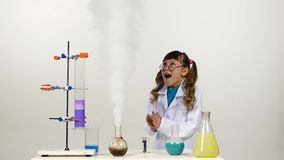 Little girl chemist with two ponytails in uniform. Cute, little with two ponytails chemist in white uniform, protective glasses and blue shirt has successfully stock video