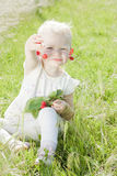 Little girl with cherries. Sitting on grass Stock Photo