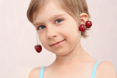 Little girl with cherries earrings. Little girl with sweet cherries royalty free stock image
