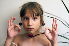 Little girl with a cherry on her ears Stock Photography