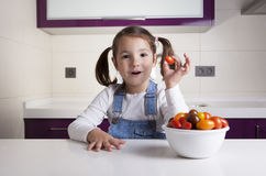 Little girl with cherry pear tomato in her hand Royalty Free Stock Photo