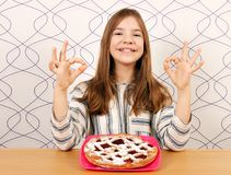 Little girl with cherry pie and ok hand sign Royalty Free Stock Photo