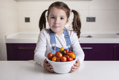 Little girl with cherry tomatoes bowl Royalty Free Stock Images