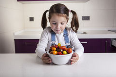Little girl with cherry tomatoes bowl Stock Image