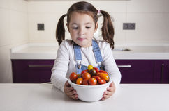 Little girl with cherry tomatoes bowl Royalty Free Stock Image