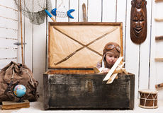 Little girl in chest with wooden plane in hands Stock Image