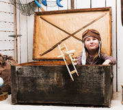 Little girl in chest with wooden plane in hands Stock Photography