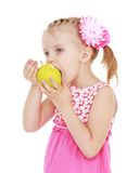 Little girl chews big green apple Stock Photo