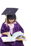 Little girl child in academician clothes looking book Atlas Stock Photos
