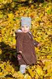 Little girl child baby in a coat and hat game makes its first steps in autumn park among fallen yellow maple leaves Stock Photo