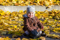 Little girl child baby crying sitting near the bag in a coat and hat game makes its first steps in autumn park among fallen yellow Royalty Free Stock Photo