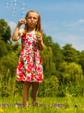 Little girl child blowing bubbles outdoor. Kid having fun in park. Happy and carefree childhood royalty free stock images