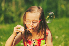 Little girl child blowing bubbles outdoor. Kid having fun in park. Happy and carefree childhood. Instagram filtered stock photo