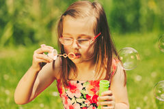 Little girl child blowing bubbles outdoor. Kid having fun in park. Happy and carefree childhood. Instagram filtered royalty free stock image