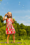 Little girl child blowing soap bubbles outdoor. Stock Images