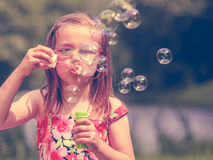 Little girl child blowing soap bubbles outdoor. Stock Photos