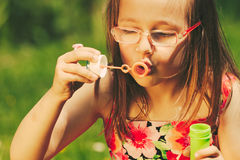 Little girl child blowing soap bubbles outdoor. Stock Photo