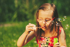 Little girl child blowing soap bubbles outdoor. Royalty Free Stock Photo