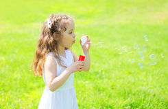 Little girl child blowing soap bubbles in summer sunny Royalty Free Stock Photo