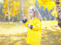Little girl child blowing soap bubbles in sunny autumn Royalty Free Stock Photos