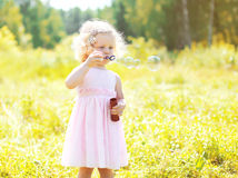 Little girl child blowing soap bubbles in sunny summer Royalty Free Stock Photography