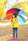 Little girl child with colorful umbrella in sunny autumn Royalty Free Stock Photos