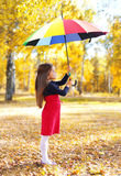 Little girl child with colorful umbrella walking in autumn Stock Photo