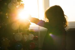 Little girl child decorate a Christmas tree against the window w stock photography
