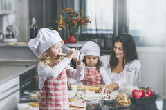 Little girl child drinks milk with her mother and sister happy c. Ook at the table in the kitchen is lovely and beautiful royalty free stock image