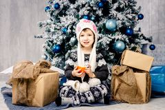 Little girl child of five years sitting on the floor near Christmas tree decorated with toys, balls. In the hands holds an orange royalty free stock photography
