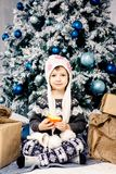 Little girl child of five years sitting on the floor near Christmas tree decorated with toys, balls. In the hands holds stock image