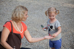 Little girl child gives the mother a toy on the alley Royalty Free Stock Photography