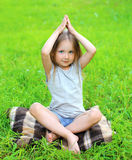 Little girl child on the grass does yoga exercise Royalty Free Stock Photography
