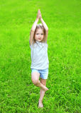 Little girl child on the grass does yoga exercise outdoors Stock Photo
