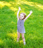 Little girl child having fun on the grass in sunny summer Royalty Free Stock Photos