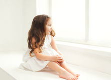 Little girl child at home in white room sitting. Near window stock photography